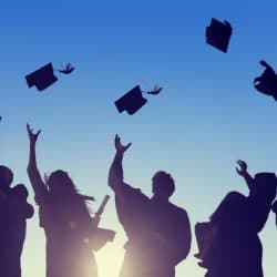 Latinos celebrating graduation throwing hats in the air with a blue sky background and sun shing through