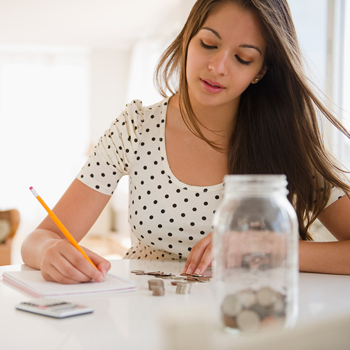woman sitting at a table with a money jar full of cash writing on a notepad