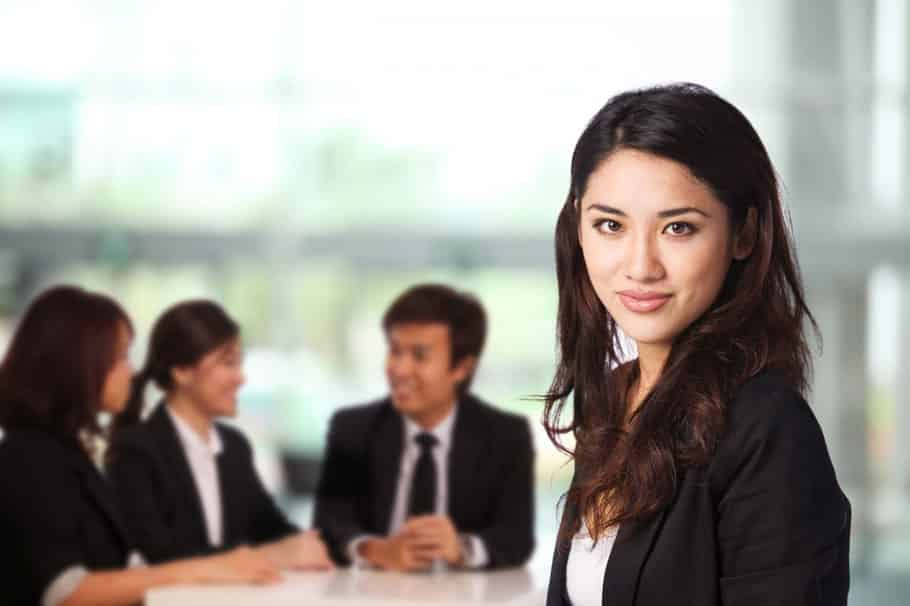 latina business woman seated at conference table with co-workers