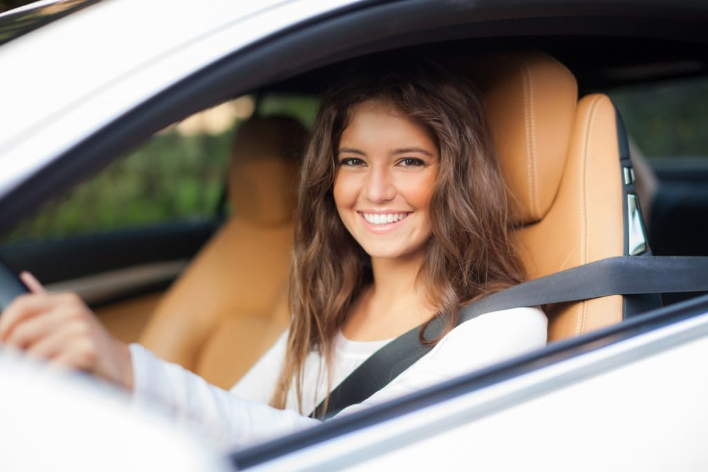 young woman driving with window down and smiling