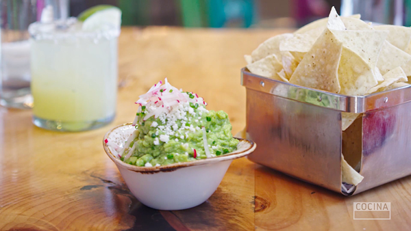 A dish of Guacamole with a side of tortilla chips-yum