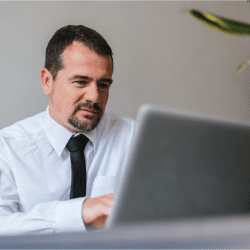 Hispanic man looking at computer monitor for online job interview