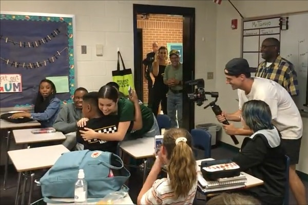 Selena Gomez hugs a surprised in classroomstudent at her old middle school