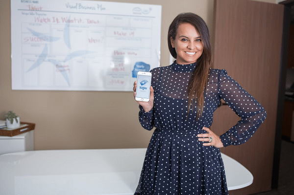 Ana Bermudez stands with one hand on her hip with the other holding her smartphone with the image of her app TAGit