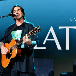 Juanes performing on stage with his guitar during a concert