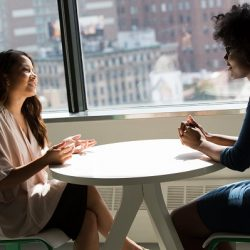 two women at work seated at a table chatting