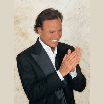 Julio Iglesias in tuxedo smiling clapping hands with joy