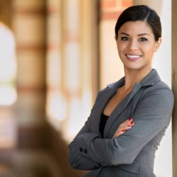 Latina business woman professional in a suit standing looking confident with arms crossed