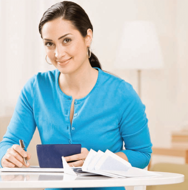 latina woman sitting at desk with checkbook and paperwork
