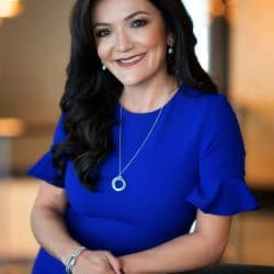 Nina Vaca dressed in blue business dress smiles while casually leaning on table