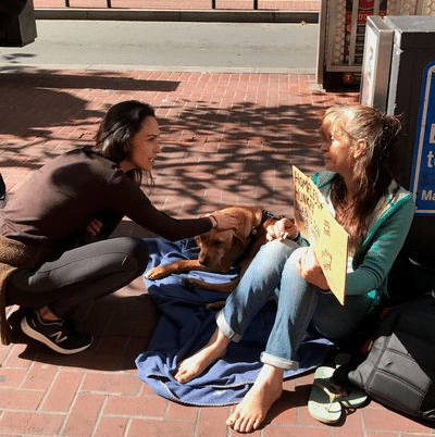 Former Wilhemina Model pictured talking homeless woman on a sidewalk holding a pet