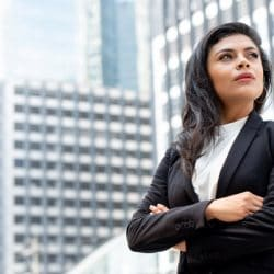 Powerful Latin businesswoman leader standing with arm crossed in city office building background