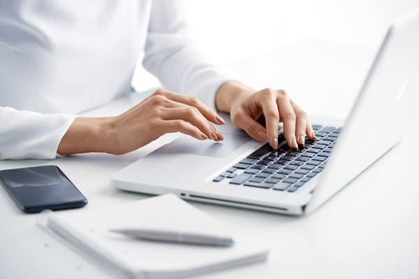 Close-up of woman's hand typing on the keyboard while sitting at desk