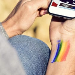 A person taking the census,holding thier smarphone with a painted pride flag drawn on their wrist