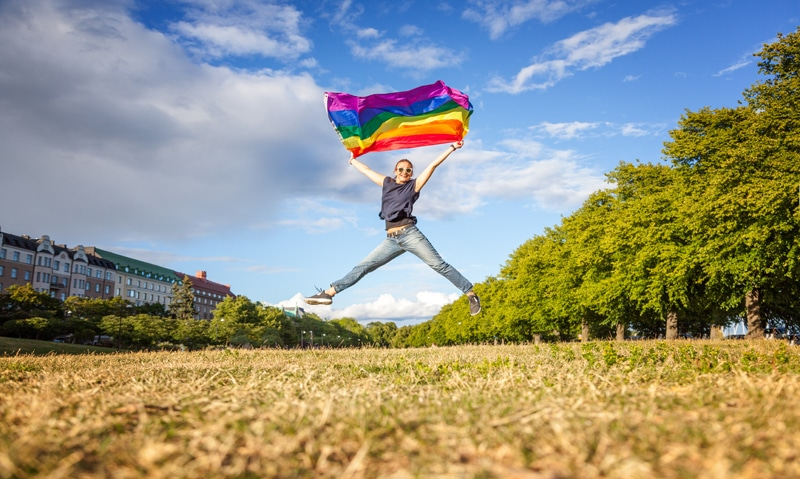 A girl jumping in the air in a field, holding a LGBT pride flag