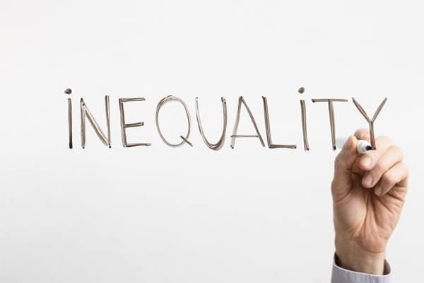 A hand writing the word Inequality on glass board,