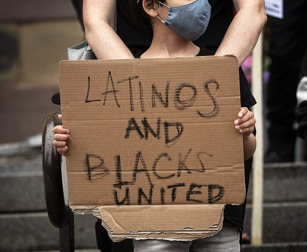 young boy holding sign that says latinos and blacks united with mother behind him and both wearing masks