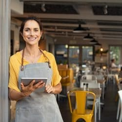 Stock image of a business woman standing outside of a cafe