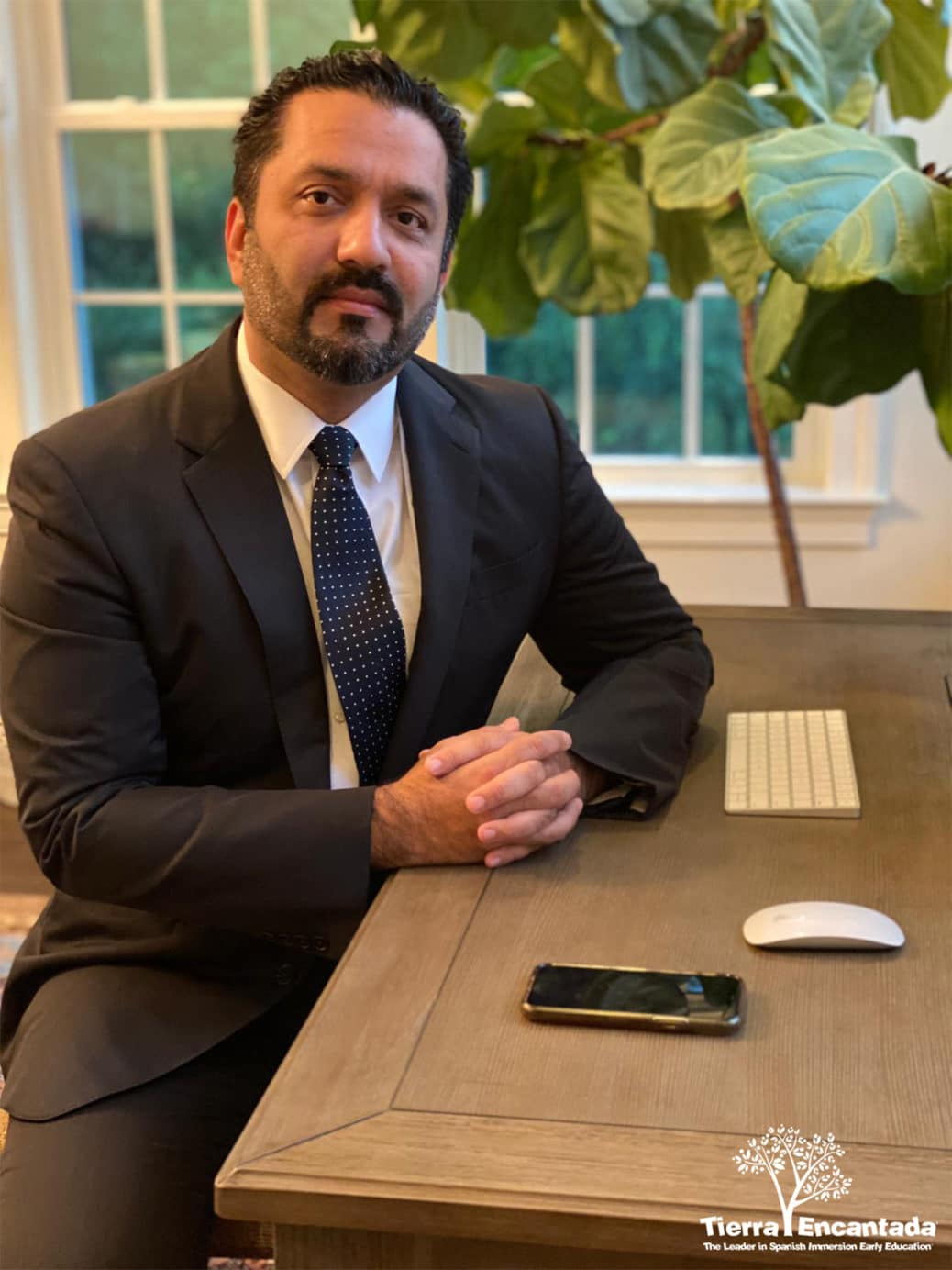 Mustafa Durrani seated at home office table wearing a suit and tie and looking confident