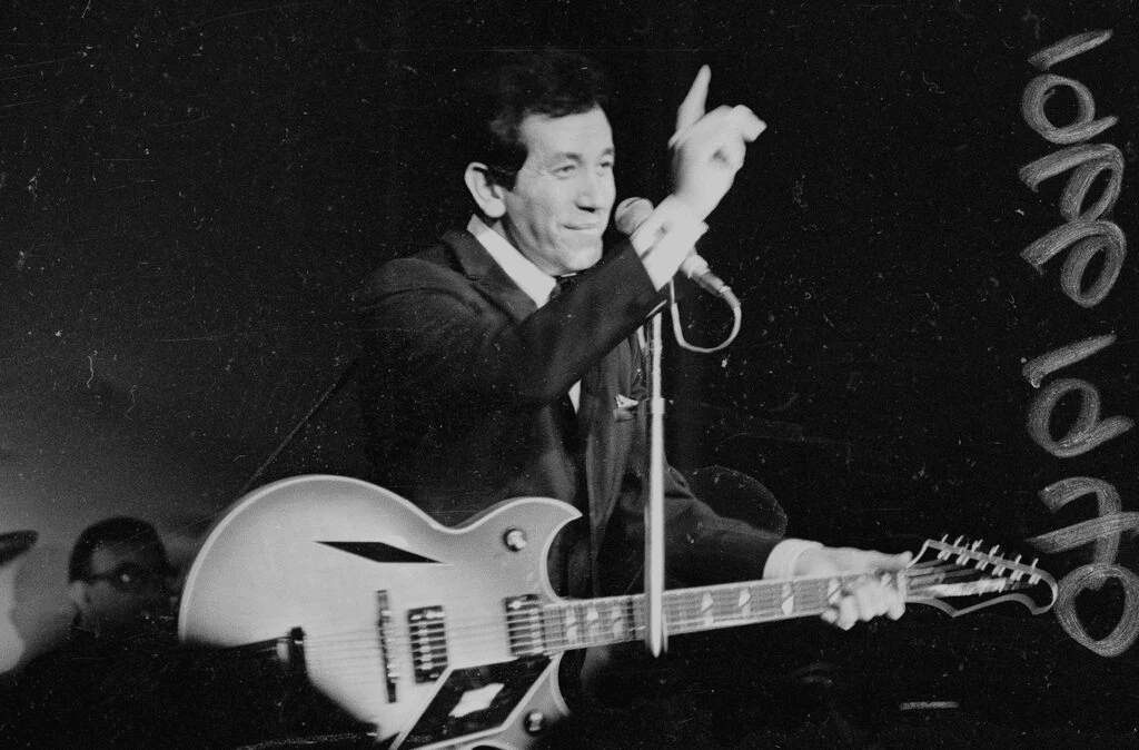 Trini Lopez onstanges in all black with guitar in hand waving to fans