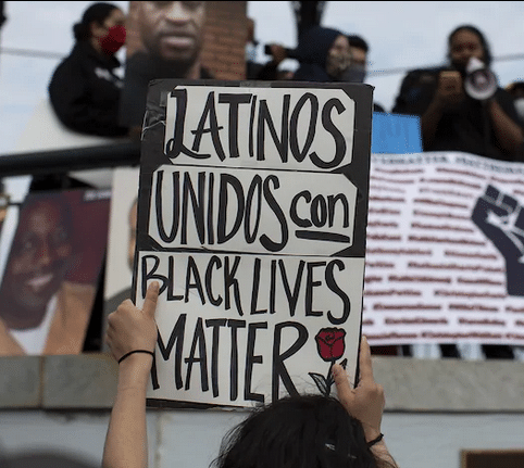 woman's hands holding sign that reads latinos and blacks united