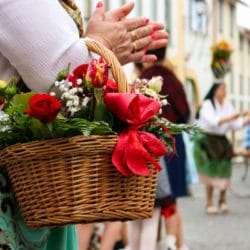 Woman in traditional clothes holding a basket full of colorful f