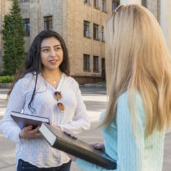 two students with books in their hands are talking at the university building