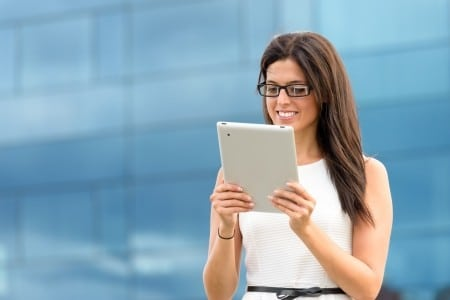 young Hispanic woman on tablet outside