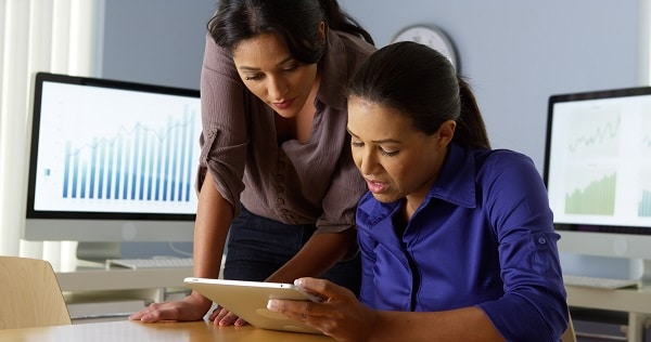 Two Latina women working together on a tablet computer