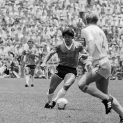 Diego Maradona on the soccer playing field kicking the ball with other players