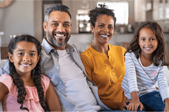 Hispanic family seated on couch together smiling