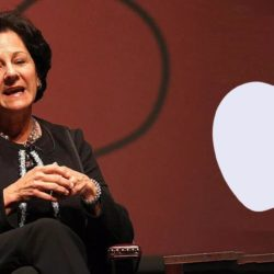 monica lozano sitting in a black suit with apple logo in the background