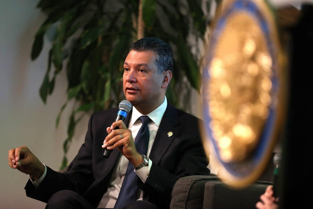 Alex Padilla wearing a black suit sitting down speaking into a microphone