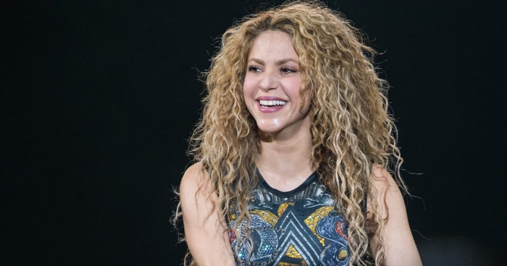 Shakira close up, smiling, blond curly hair