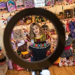 """Amaury Vidales holds a shirt with a number so viewers of her """"Amaury's Accessories"""" livestream can comment and purchase the shirt through a Facebook Live event inside of her Eden Prairie, Minn., home on March 10."""