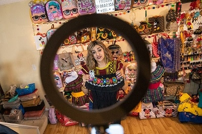 "Amaury Vidales holds a shirt with a number so viewers of her ""Amaury's Accessories"" livestream can comment and purchase the shirt through a Facebook Live event inside of her Eden Prairie, Minn., home on March 10."
