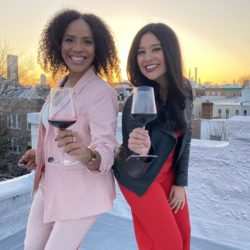 two women smile at the camera and hold a glass of wine as the sun sets in the background