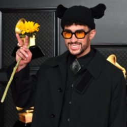Bad Bunny holding a sunflower in front of the grammy award red carpet entrance wearing a bunny ear beanie on his head after winning best latin pop album