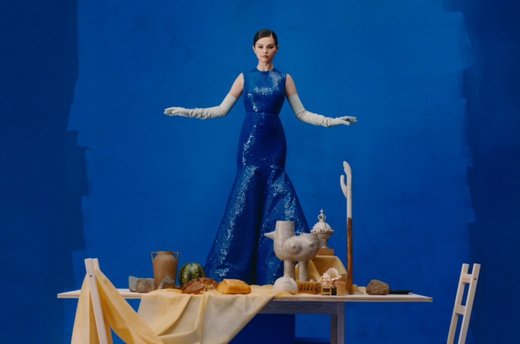 Selena Gomez pictured in an all blue dress against a blue background with a dining table in front of her filled with food and art pieces