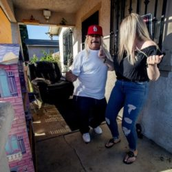 Genaro Rangel wears a wig and dances with his daughter Wendy on their porch in Santa Ana.