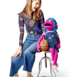 Romina Puga sitting with her two co host puppets on a stool