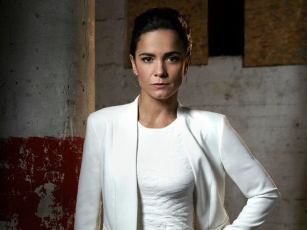 Alice Braga pictured in a white top with a white blazer coat posing with her left hand on her hip and her hair in a pony tail