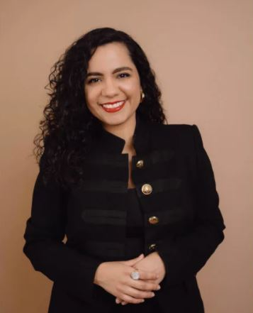 Investing Latina Founder Jully-Alma Taveras pictures in front of a brown backgrop while wearing a black blazer