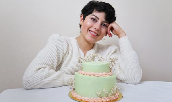 Lara de la Rosa wearing a white sweater and smiling in front of the camera while she leans on her left hand in front of a mint green cake with pink icing and flowers.
