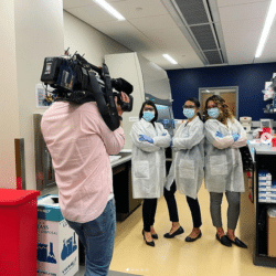 three latina scientists in lab coats standing in the lab together looking confident with arms folded
