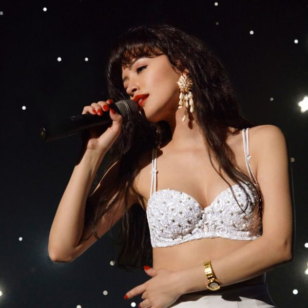Christian Serratos performing as Selena in the netflix series wearing a white bralette top, gold dangly earrings and red lipstick.