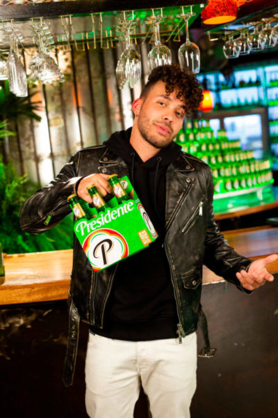 Prince Royce pictures holding a six pack of Presidente beet in front of a brewery bar